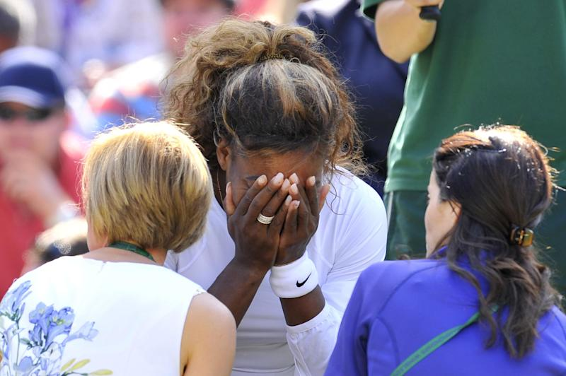 US player Serena Williams (C) covers her face as she talks to the doctor on court after being taken ill during her women's doubles second round match at Wimbledon on July 1, 2014