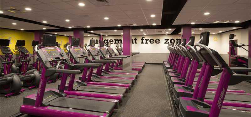 Rows of treadmills inside a Planet Fitness.