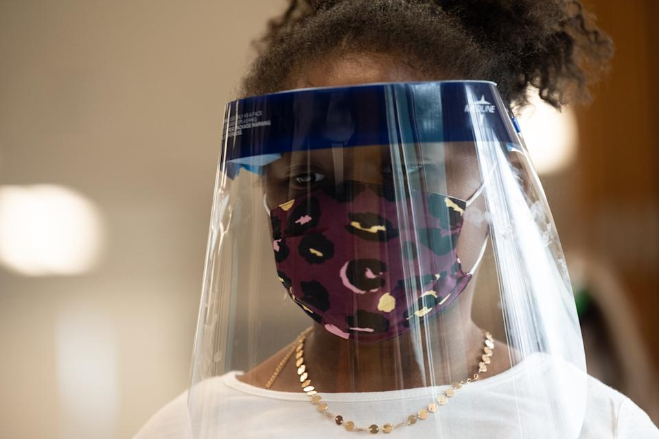 A child wearing a face shield and mask stands in the cafeteria of Medora Elementary School in Louisville, Ky. (Jon Cherry/Getty Images)