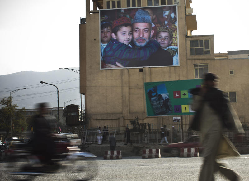 Afghans pass by a giant poster of Afghanistan's President Hamid Karzai in the center of Kabul, Afghanistan, Wednesday, Oct 31, 2012. Presidential elections considered crucial to Afghanistan's security and stability will be held on schedule in April 2014, the country's election commission announced Oct 31. The decision eased concerns that President Hamid Karzai would seek to delay the election despite his repeated assurances that he would not. (AP Photo/Anja Niedringhaus)