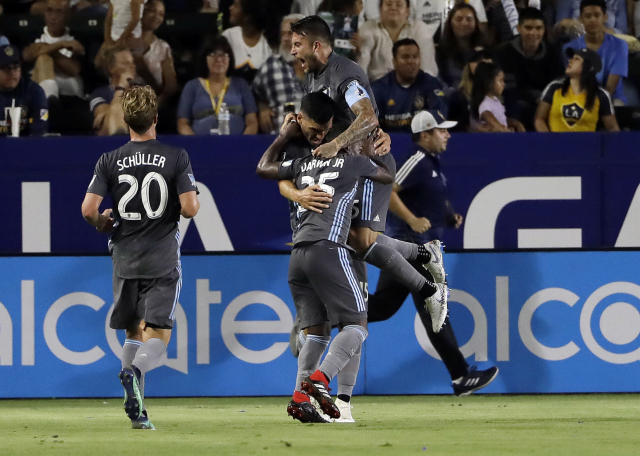 Minnesota United's Michael Boxall, center, is hugged by teammates Francisco Calvo, top right, and Carlos Darwin Quintero (25) after Boxall's goal against the LA Galaxy during the second half of an MLS soccer match Saturday, Aug. 11, 2018, in Carson, Calif. (AP Photo/Marcio Jose Sanchez)