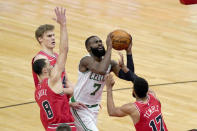 Boston Celtics guard Jaylen Brown (7) shoots between Chicago Bulls' Zach LaVine (8) Garrett Temple (17) and Lauri Markkanen during the first half of an NBA basketball game Monday, Jan. 25, 2021, in Chicago. (AP Photo/Charles Rex Arbogast)