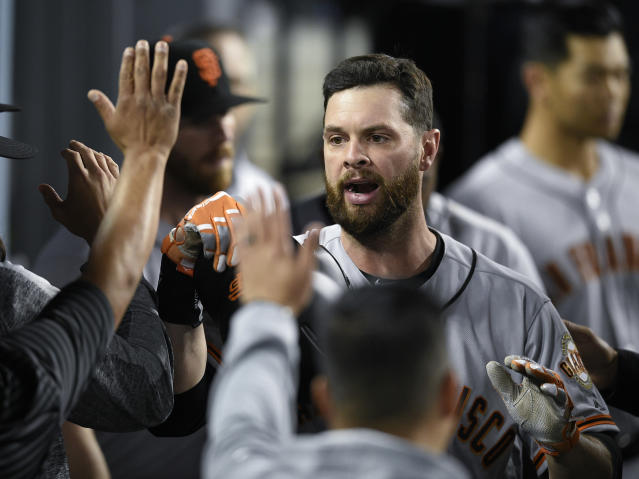 San Francisco Giants' Brandon Belt celebrates with the dugout after a solo home run during the sixth inning of a baseball game against the Los Angeles Dodgers in Los Angeles, Monday, April 1, 2019. (AP Photo/Kelvin Kuo)