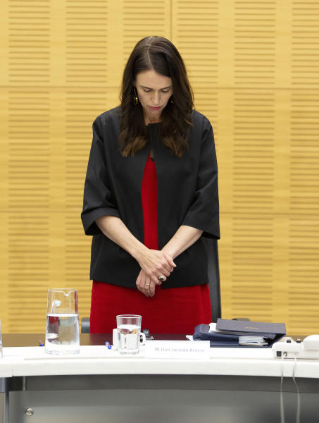 New Zealand Prime Minister Jacinda Ardern observes a moment of silence with her cabinet colleagues at the moment that a volcano erupted a week earlier, killing 18 people and leaving others with severe burns, in Wellington, New Zealand, Monday, Dec. 16, 2019. Ardern said that wherever people were in New Zealand or around the world, it was an opportunity to stand alongside those who had lost loved ones in the tragedy at White Island on Monday, Dec. 9. (Hagen Hopkins/Pool Photo via AP)