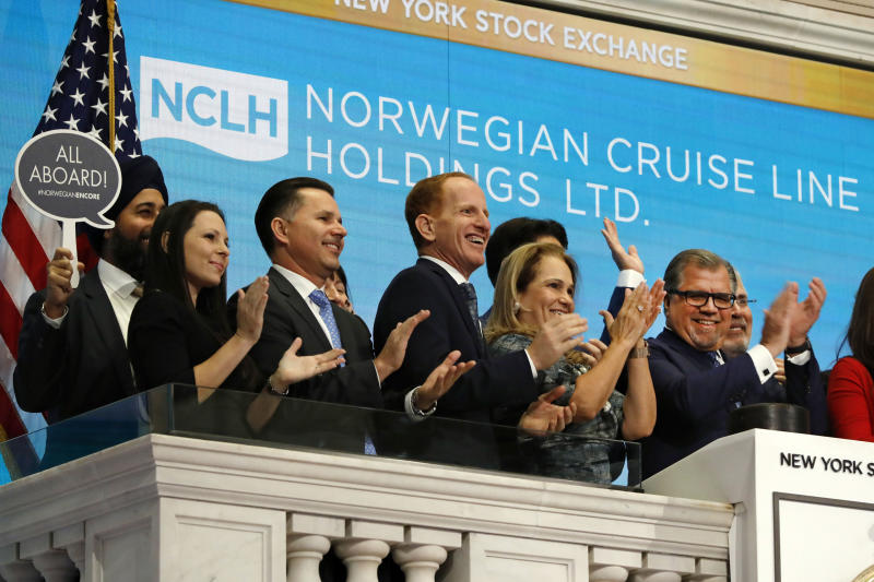 Norwegian Cruise Line Holdings President & CEO Frank Del Rio, right, joins applause as he rings the New York Stock Exchange opening bell, Tuesday, Nov. 12, 2019, to celebrate the launch of their newest ship, the Norwegian Encore. (AP Photo/Richard Drew)