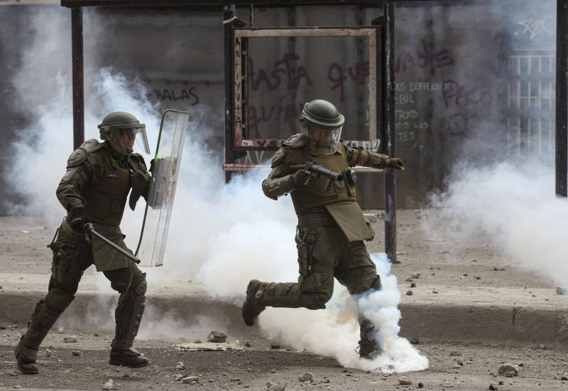 Chilean kicks a tear gas canister during clashes with anti-government protesters in Santiago, Chile, Monday, Nov. 18, 2019. According to the Medical College of Chile at least 230 people have lost sight after being shot in an eye in the last month while participating in the demonstrations over inequality and better social services. (AP Photo/Esteban Felix)