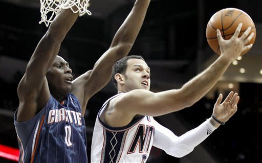 New Jersey Nets' Jordan Farmar, right, goes up for a shot against Charlotte Bobcats' Bismack Biyombo during the first quarter of an NBA basketball game, Sunday, Jan. 22, 2012, in Newark, N.J. (AP Photo/Julio Cortez)