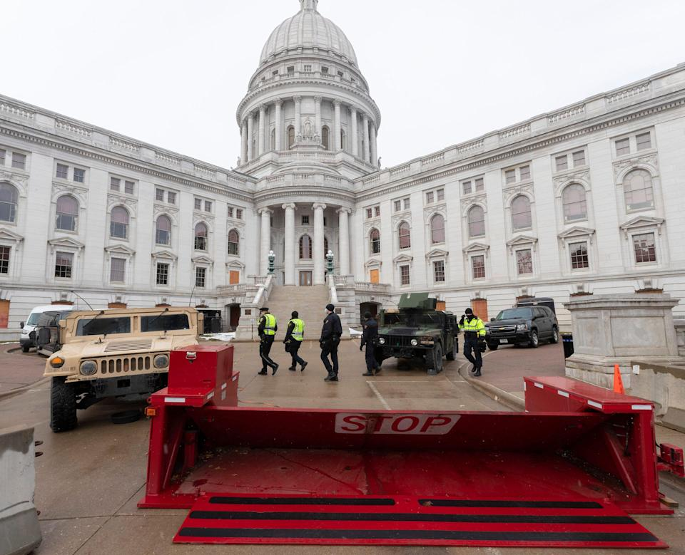 Law enforcement personnel walk past Wisconsin National Guard vehicles and a barricade on Sunday at the Wisconsin State Capitol in Madison.