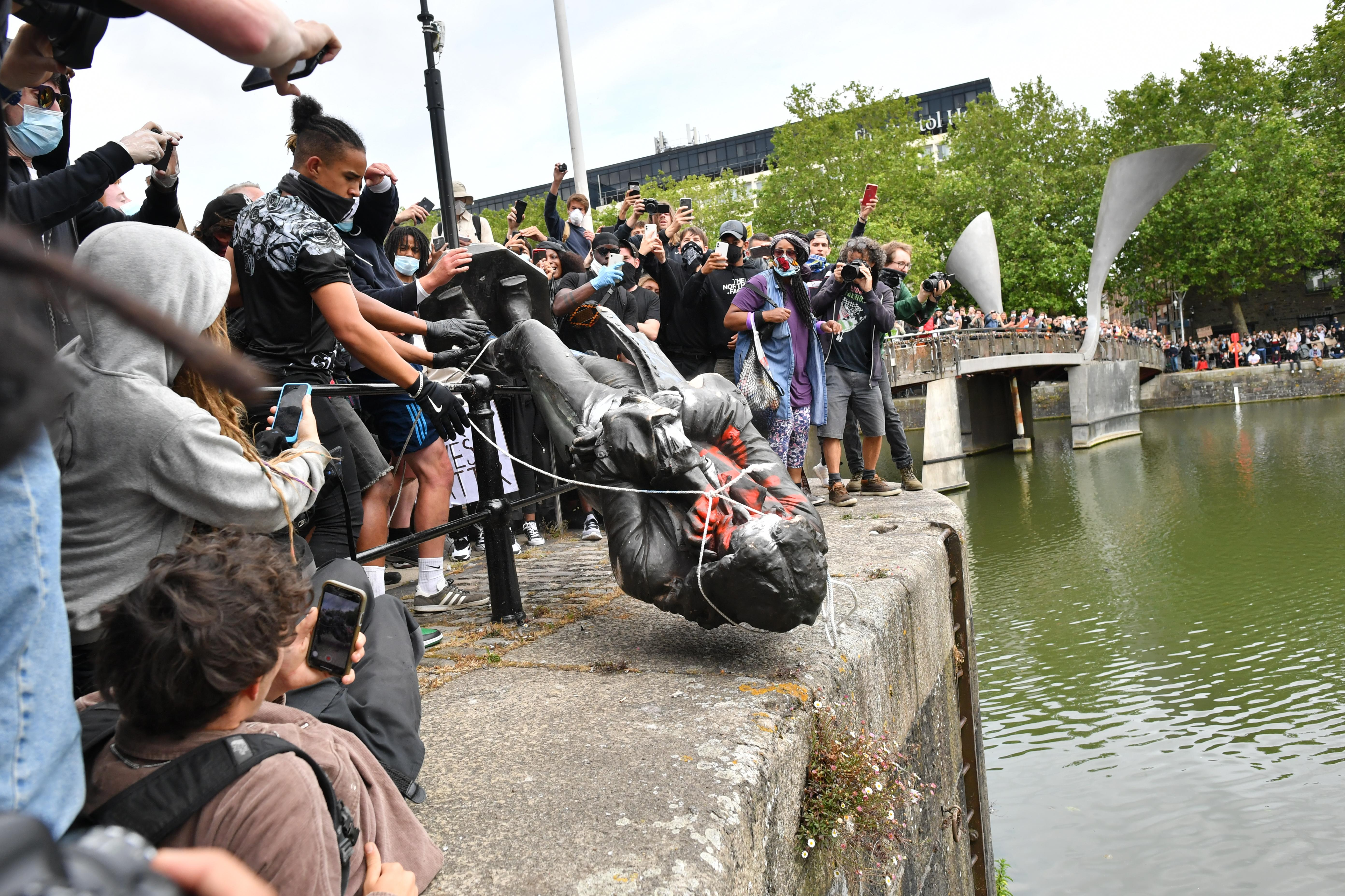 Protesters throw statue of Edward Colston into Bristol harbour during a Black Lives Matter protest rally, in memory of George Floyd who was killed on May 25 while in police custody in the US city of Minneapolis.