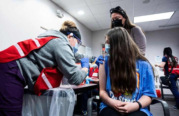 A mother looks on as her daughter gets a Covid-19 vaccination in Virginia on 13 May, 2021. A new poll has found that a quarter of adults in the United States do not intend to get their children vaccinated against Covid-19 (AFP via Getty Images)