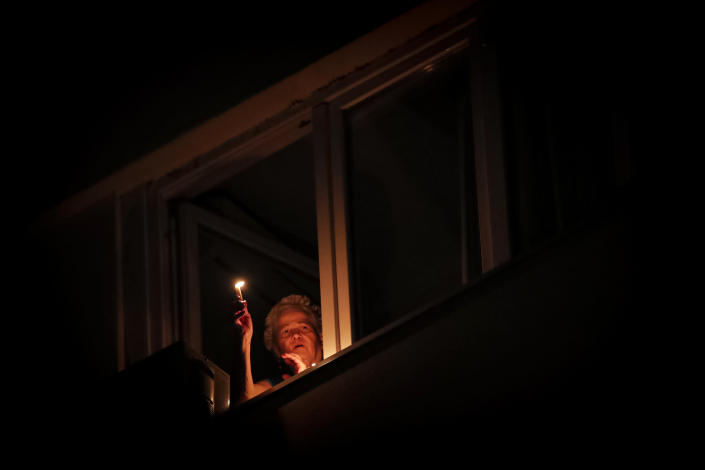 A woman holds a candle at the window while listening to the blessings of a priest from downstairs during the coronavirus pandemic in Bucharest, Romania, Saturday, April 18, 2020. Priests accompanied by volunteers distributed the holy light ahead of the usual time, at midnight, as people observed the interdiction to join religious celebrations in the week leading to the Orthodox Easter, imposed across Romania as authorities try to limit the spread of the COVID-19 infections. (AP Photo/Vadim Ghirda)