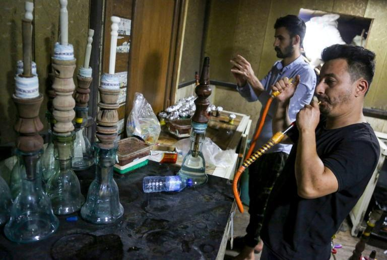 Employees prepare waterpipes for customers at a coffee shop in Iraq's holy city of Karbala -- complete with the locally carved wooden section