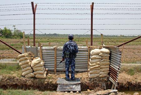 Myanmar Border Guard Police officer keeps watch near the Taung Pyo Letwe reception camp overlooking the border with Bangladesh