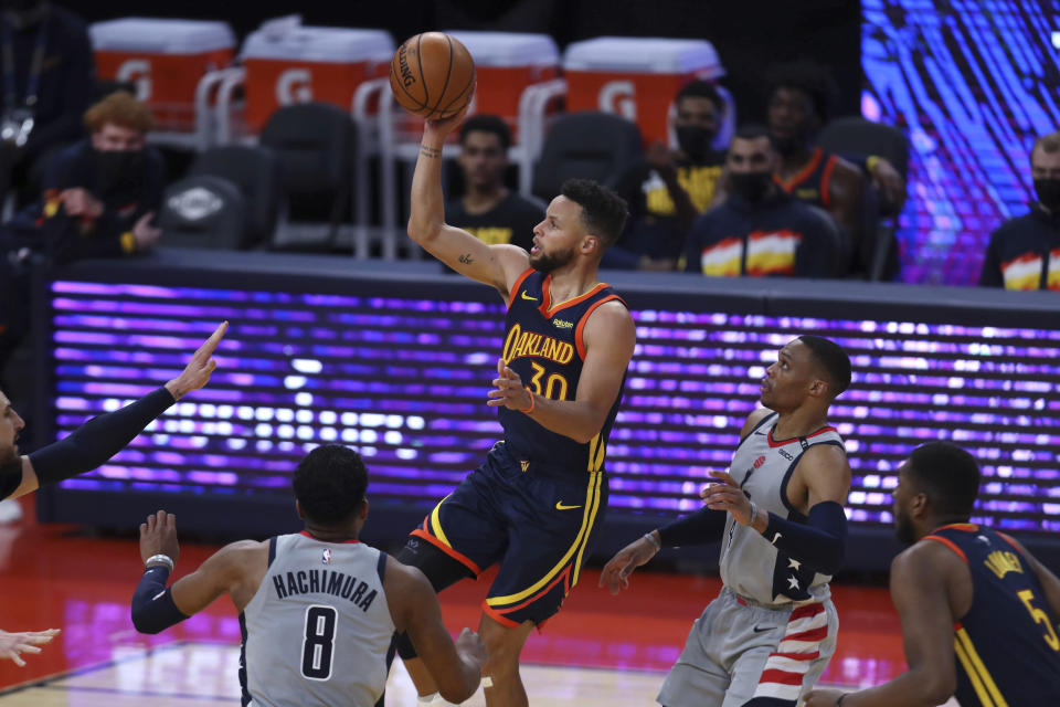 Golden State Warriors guard Stephen Curry, center, shoots against Washington Wizards forward Rui Hachimura, left, and guard Russell Westbrook, right, during the first half of an NBA basketball game in San Francisco, Friday, April 9, 2021. (AP Photo/Jed Jacobsohn)