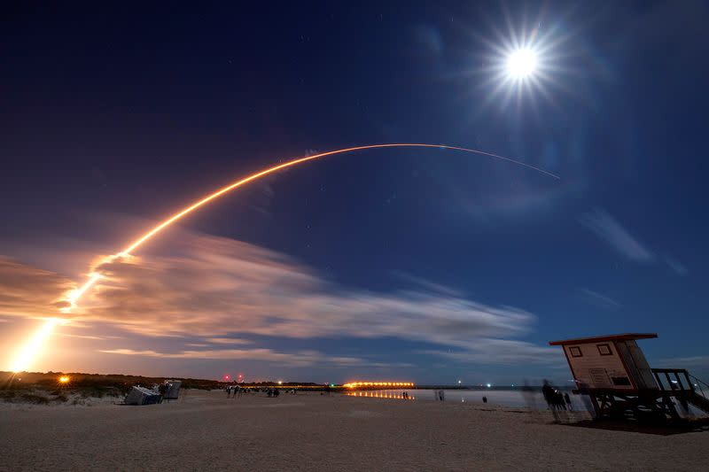 The Solar Orbiter spacecraft, built for NASA and the European Space Agency, lifts off from pad 41 aboard a United Launch Alliance Atlas V rocket as the full moon is seen above at the Cape Canaveral Air Force Station in Cape Canaveral