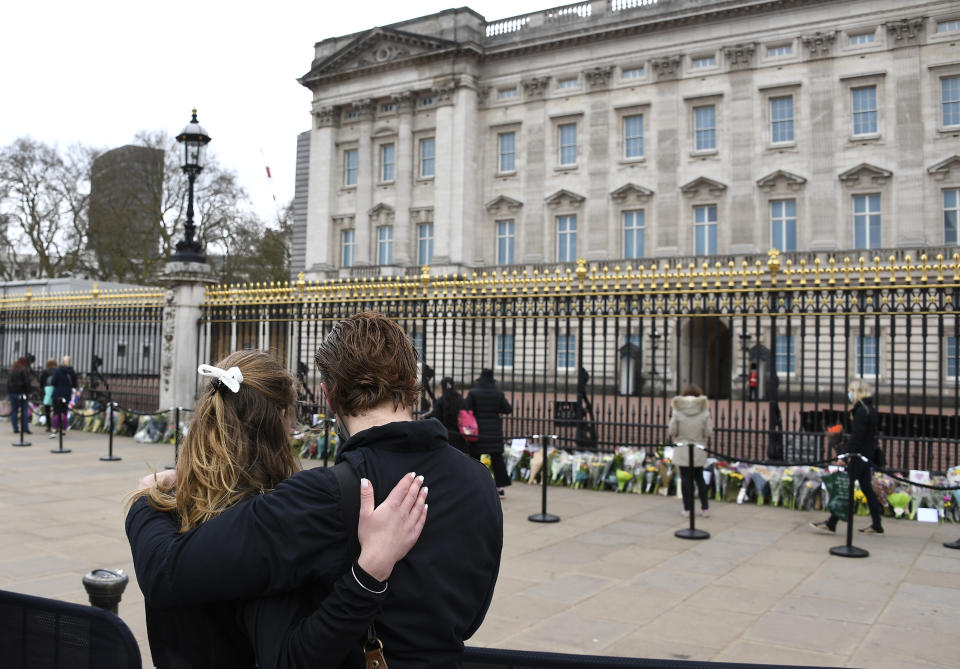Two people stand behind a barrier as they view flower tributes left in front of the gate at Buckingham Palace in London, a day after the death of Britain's Prince Philip, Saturday, April 10, 2021. Britain's Prince Philip, the irascible and tough-minded husband of Queen Elizabeth II who spent more than seven decades supporting his wife in a role that mostly defined his life, died on Friday. (AP Photo/Alberto Pezzali)