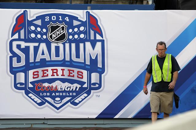 A worker walks past the event banner at Dodger Stadium as preparations continue for the upcoming 2014 NHL Stadium Series hockey game at Dodger Stadium in Los Angeles, Wednesday, Jan. 22, 2014. The Los Angeles Kings and Anaheim Ducks will play outdoors at Dodger Stadium next Saturday, Jan. 25th. (AP Photo/Nick Ut)