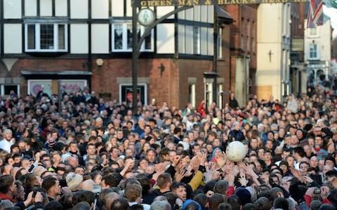 Competitors reach for the ball during the annual Royal Shrovetide Football Match in Ashbourne - Credit: AFP/Getty Images