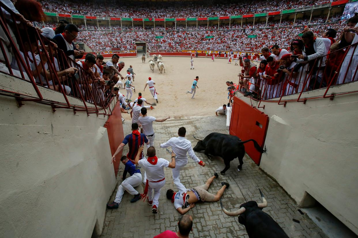 An unidentified runner appears to lie unconscious near the bullring as other runners and bulls trample him. (Photo: Pablo Blazquez Dominguez via Getty Images)