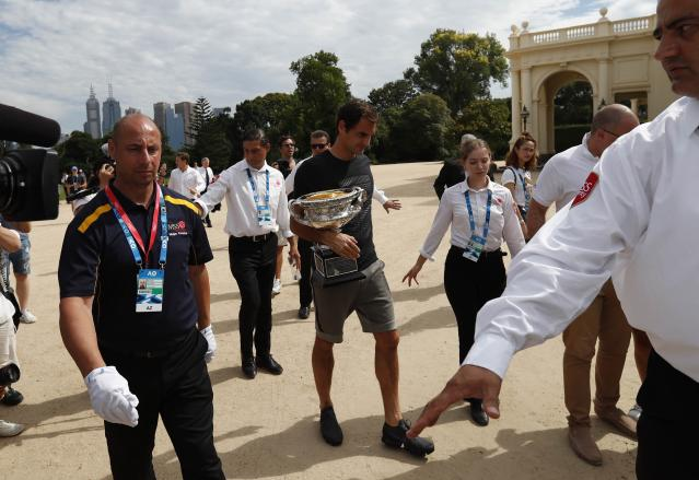 Tennis - Australian Open - Melbourne, Australia, January 29, 2018. Roger Federer of Switzerland walks with the men's singles trophy as he leaves while surrounded by security guards after the winner's photoshoot at the government house in Melbourne, Australia. REUTERS/Issei Kato
