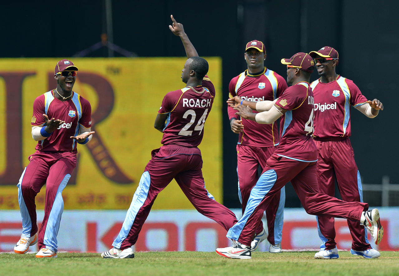 West Indies bowler Kemar Roach (C) celebrates with teammates after bowling out Sri Lankan cricketer Dinesh Chandimal during the fifth match of the Tri-Nation series between Sri Lanka and West Indies at the Queen's Park Oval in Port of Spain on July 7, 2013. West Indies won the toss and elected to field. AFP PHOTO/Jewel Samad