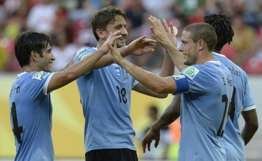 Uruguay's midfielder Diego Perez (R) celebrates with teammates Nicolas Lodeiro (L) and Gaston Ramirez after scoring against Tahiti during their FIFA Confederations Cup Brazil 2013 Group B football match, at the Pernambuco Arena in Recife on June 23, 2013. AFP PHOTO / JUAN BARRETO (AFP | Juan Barreto)