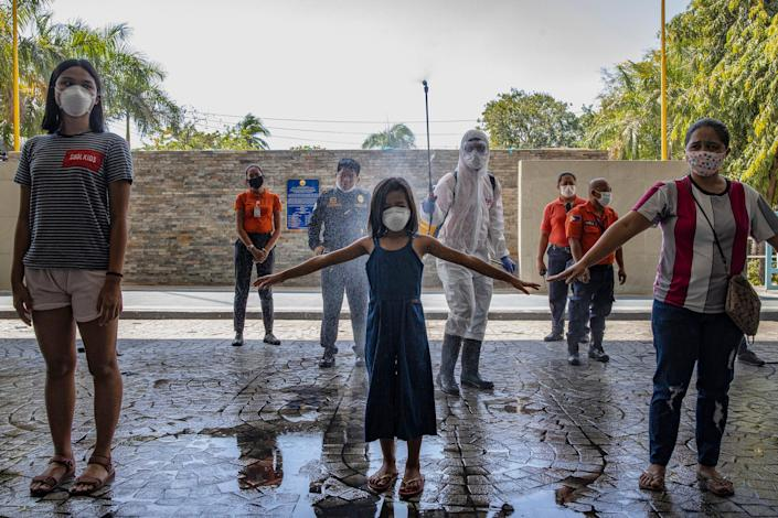 Visitors are sprayed with disinfectant before entering a government office building to curb the spread of COVID-19 on March 19, 2020 in Pasig city, Metro Manila, Philippines.