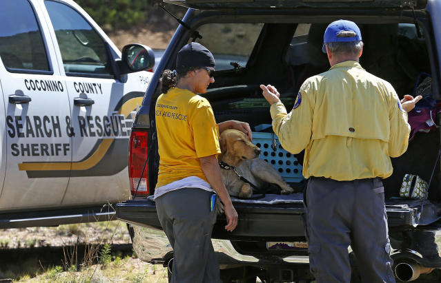 <p>Members of the Coconino County Search and Rescue Team take a break near the entrance to the First Crossing recreation area during the search and rescue operation for a victim in a flash flood along the banks of the East Verde River Monday, July 17, 2017, in Payson, Ariz. The bodies of several children and adults have been found after Saturday's flash flooding poured over a popular swimming area in the Tonto National Forest. (AP Photo/Ross D. Franklin) </p>