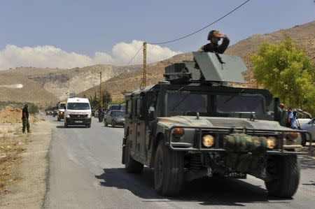 Lebanese army soldiers escort ambulances believed to be carrying casualties as they return from the Sunni Muslim border town of Arsal, in eastern Bekaa Valley August 5, 2014. REUTERS/Hassan Abdallah