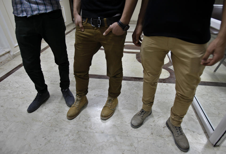 """Mohammed Hanouna, Tareq Naqib and Ayman al-Sayed, """"from left to right"""" show their tight trousers in Gaza City, Sunday, April 7, 2013. Al-Sayed and Naqib had their heads shaved by Hamas police during a crackdown on long or gel-styled spiky hair, the latest attempt by Hamas to impose its hardline version of Islam on Gaza. The young men say the tight-fitting, narrow-leg pants they are wearing are also outlawed under the new rules. (AP Photo/Adel Hana)"""