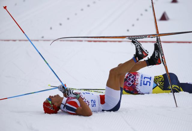 Norway's Chris Andre Jespersen and Kazakhstan's Alexey Poltoranin (R) lie on the ground after crossing the finish line in the men's cross-country 15km classic event at the 2014 Sochi Winter Olympics February 14, 2014. REUTERS/Kai Pfaffenbach (RUSSIA - Tags: OLYMPICS SPORT SKIING)