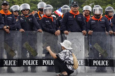 A woman takes pictures in front of a line of policemen blocking protesters against an amnesty bill, on the main road near the government and parliament buildings in central Bangkok November 7, 2013. REUTERS/Kerek Wongsa