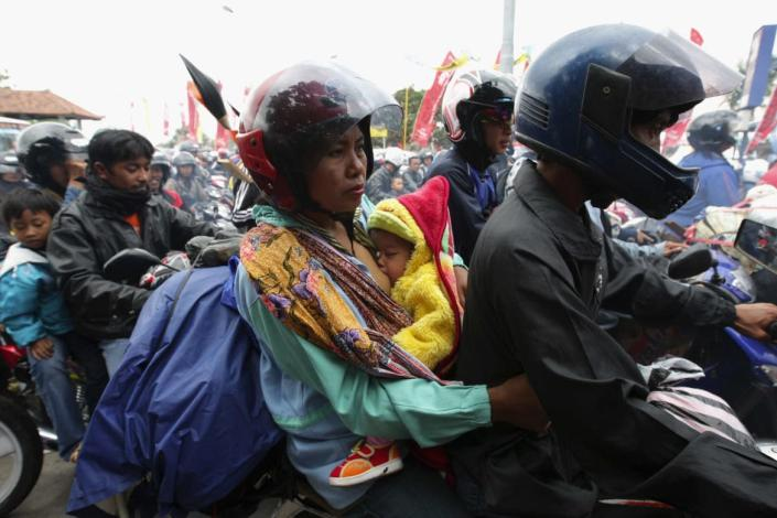 """<div class=""""inline-image__caption""""> <p>A mother breastfeed her baby on a motorcycle in Gilimanuk, Bali Island, Indonesia. </p> </div> <div class=""""inline-image__credit""""> Dimas Ardian/Getty </div>"""