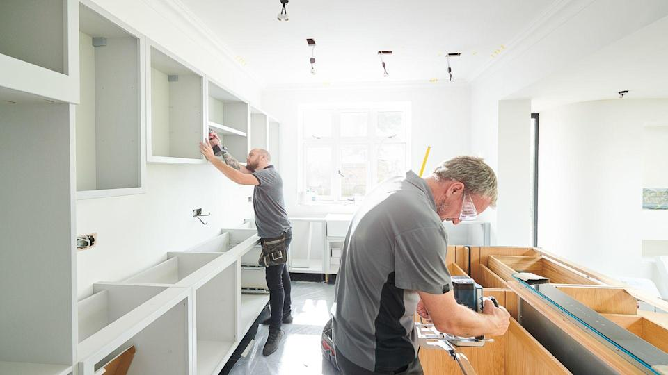 two joiners installing a kitchen.