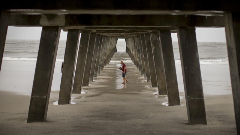 Danny James walks under the Tybee Island pier with a hat full of sea shells he collected during low tide as Hurricane Dorian passes 80 miles out to sea, Sept. 5, 2019, in Tybee Island, Ga. (Photo: Stephen B. Morton/AP)
