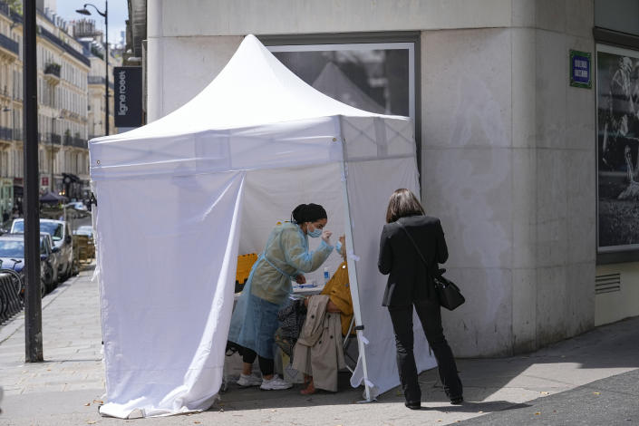 A medical technician administers nasal swabs at a mobile testing site in Paris, Monday, July 12, 2021. France's President Emmanuel Macron is hosting a top-level virus security meeting Monday morning and then giving a televised speech Monday evening, the kind of solemn speech he's given at each turning point in France's virus epidemic.(AP Photo/Michel Euler)