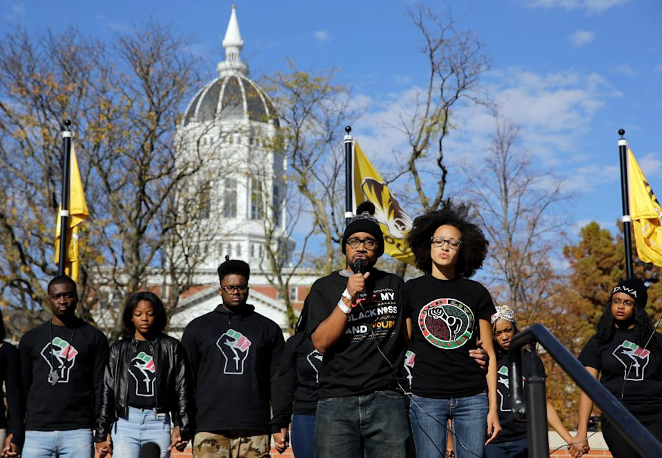 FILE - In this Nov. 9, 2015, file photo, graduate student Jonathan Butler, center, addresses a crowd following the announcement that University of Missouri System President Tim Wolfe would resign, in Columbia, Mo. On the day he met with black players for the University of Missouri's football team, Butler hadn't eaten for six days. (AP Photo/Jeff Roberson, File)