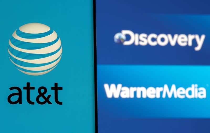 AT&T logo is seen on a smartphone in front of displayed Discovery and Warner Media logos in this illustration