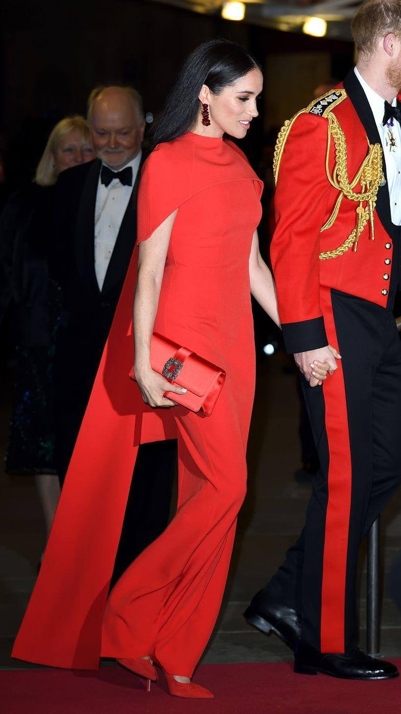 """<p>When Meghan and Prince Harry attended the <a href=""""https://www.townandcountrymag.com/society/tradition/a31270213/meghan-markle-prince-harry-formal-uniform-standing-ovation-photos/"""" rel=""""nofollow noopener"""" target=""""_blank"""" data-ylk=""""slk:Mountbatten Festival of Music"""" class=""""link rapid-noclick-resp"""">Mountbatten Festival of Music</a> at London's Royal Albert Hall, she wore a series of <a href=""""https://www.townandcountrymag.com/style/fashion-trends/a31351877/meghan-markle-final-royal-fashion-bold-looks/"""" rel=""""nofollow noopener"""" target=""""_blank"""" data-ylk=""""slk:bold monochrome outfits"""" class=""""link rapid-noclick-resp"""">bold monochrome outfits</a>, including this <a href=""""https://www.townandcountrymag.com/society/tradition/a31262662/meghan-markle-red-gown-mountbatten-music-festival-photos/"""" rel=""""nofollow noopener"""" target=""""_blank"""" data-ylk=""""slk:scarlet Safiyaa cape dress"""" class=""""link rapid-noclick-resp"""">scarlet Safiyaa cape dress</a>. She paired the gown with a matching satin Manolo Blahnik clutch, Stuart Weitzman pumps, and Simone Rocha beaded drop earrings. <br></p>"""