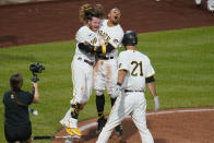 Pittsburgh Pirates' Wilmer Difo, back right, and Ben Gamel, back left, celebrate after Difo scored from second on a groundout by Colin Moran to give the Pirates a 5-4 win in a baseball game against the Cincinnati Reds in Pittsburgh, Wednesday, Sept. 15, 2021. (AP Photo/Gene J. Puskar)