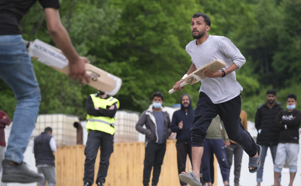 Players cross for a run as migrants play a game of cricket in Blazuj migrant camp in Bosnia's capital of Sarajevo Wednesday, May 19, 2021. (AP Photo/Kemal Softic)