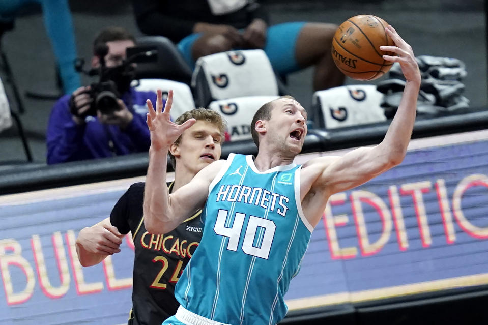 Charlotte Hornets' Cody Zeller (40) grabs a rebound over Chicago Bulls' Lauri Markkanen during the first half of an NBA basketball game Thursday, April 22, 2021, in Chicago. (AP Photo/Charles Rex Arbogast)