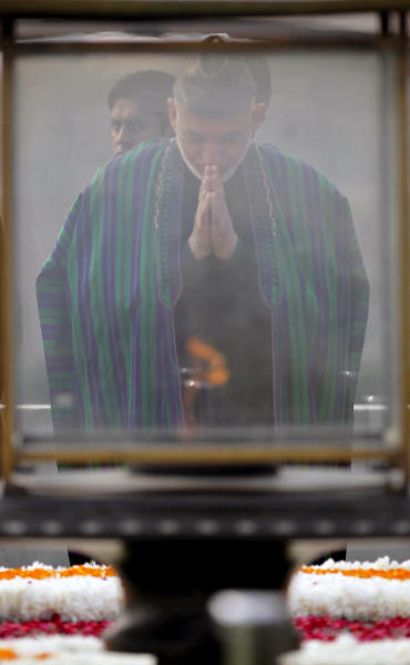 Afghanistan's President Hamid Karzai offers prayers at Mahatma Gandhi memorial in New Delhi, India, Monday, Nov. 12, 2012. Karzai was meeting with Indian leaders Monday in a bid to woo investment to his war-torn country and boost security before a planned drawdown of NATO troops in 2014. (AP Photo/Mustafa Quraishi)