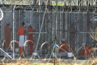 FILE - In this Feb. 2, 2002, file photo detainees from Afghanistan sit in their cells at Camp X-Ray at the U.S. Naval Base in Guantanamo Bay, Cuba. At the time the image was taken there were 158 al-Qaida and Taliban prisoners being held at the camp. The White House says it intends to shutter the prison on the U.S. base in Cuba, which opened in January 2002 and where most of the 39 men still held have never been charged with a crime. (AP Photo/Lynne Sladky, File)