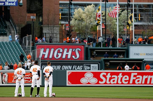 BALTIMORE, MD - APRIL 16: Outfielders Nate McLouth #9 (L), Adam Jones #10 (C), and Nick Markakis #21 of the Baltimore Orioles observe a moment of silence to honor the victims of the Boston Marathon bombing before the start of their game against the Tampa Bay Rays at Oriole Park at Camden Yards on April 16, 2013 in Baltimore, Maryland. All uniformed members of both teams are wearing jersey number 42 in honor of Jackie Robinson Day. (Photo by Rob Carr/Getty Images)