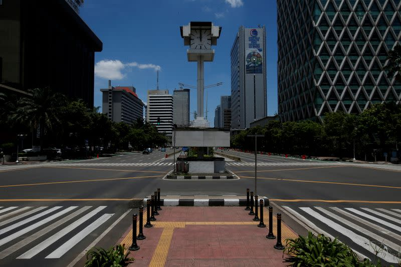 FILE PHOTO: An almost empty intersection with low traffic is seen at noon on Jalan M.H. Thamrin, one of the main roads in Jakarta, during the coronavirus disease (COVID-19) outbreak, in Jakarta
