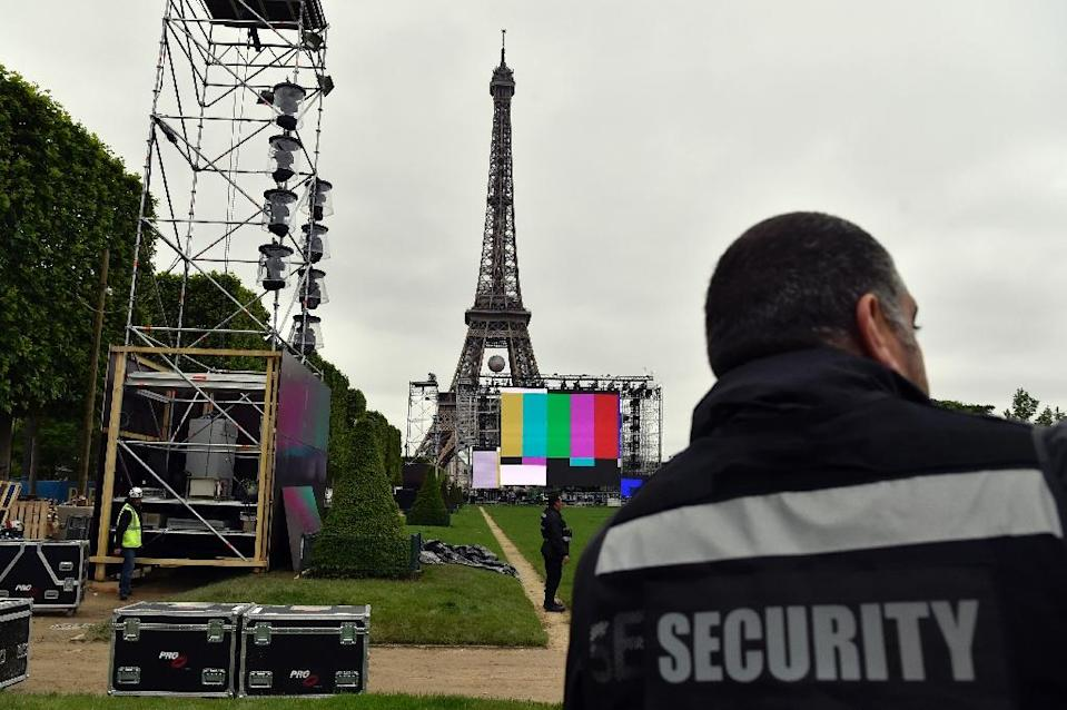 """A security guard watches the UEFA Euro 2016 fan zone site under construction next to the Eiffel Tower at the """"Champs de Mars"""", in Paris on June 3, 2016 (AFP Photo/Alain Jocard)"""