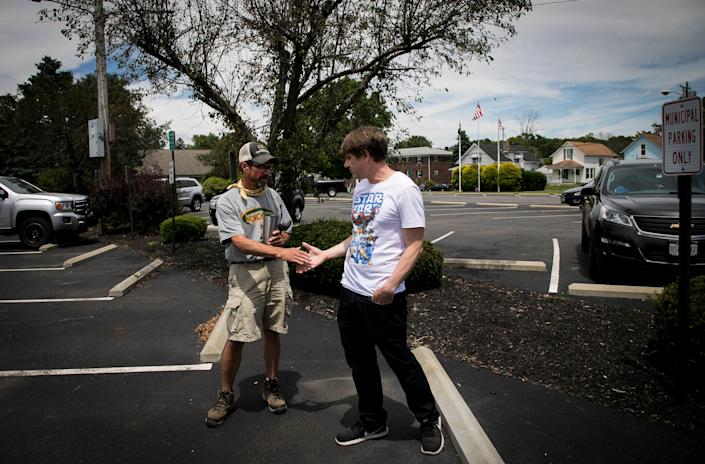 Wayne Sulken and Chris Karnes, both Bethel residents, shake hands after having a discussion in the parking lot of the Bethel Municipal Building on Tuesday, June 16.