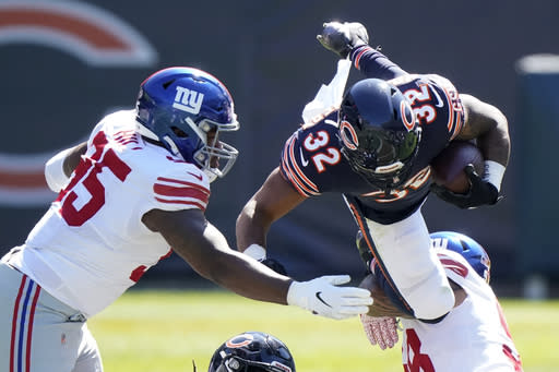 Chicago Bears running back David Montgomery (32) is brought down by New York Giants nose tackle Austin Johnson (98) as defensive end B.J. Hill (95) assists during the first half of an NFL football game in Chicago, Sunday, Sept. 20, 2020. (AP Photo/Nam Y. Huh)
