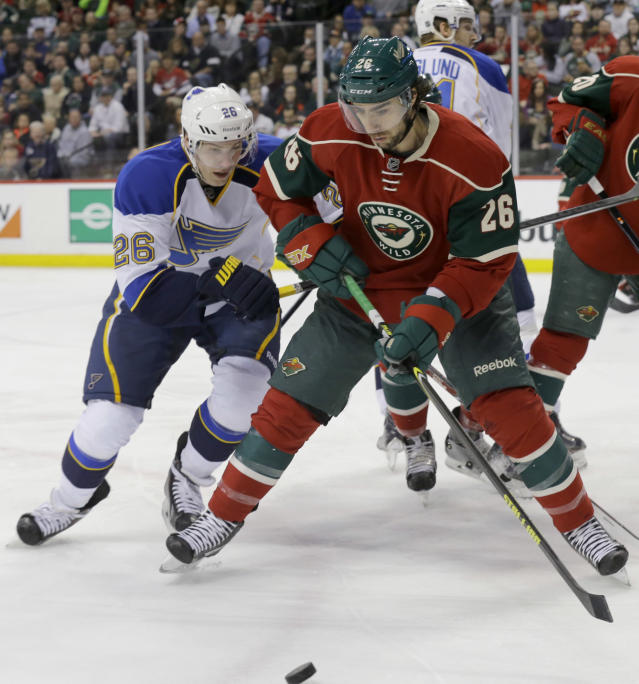 St. Louis Blues right wing Dmitrij Jaskin, left, of Russia, and Minnesota Wild left wing Matt Moulson chase the puck during the second period of an NHL hockey game in St. Paul, Minn., Thursday, April 10, 2014. (AP Photo/Ann Heisenfelt)